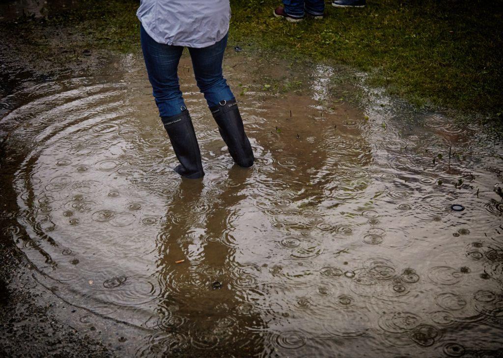 Hvordan forebygge fuktskader, dame med støvler stående i vanndam
